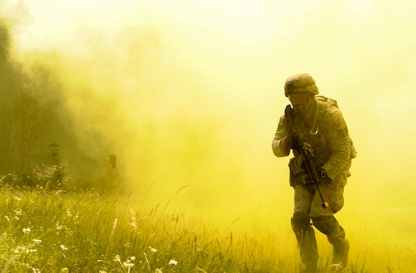 Staff Sgt. Eric Jeffcoat, 100th Security Forces Squadron base defense operation center controller, emerges from smoke grenade smoke during 435th SFS's Ground Combat Readiness Training Center Security Operations Course at U.S. Army Garrison Baumholder, Germany, June 15, 2017. Conducting missions as a team and being evaluated by the 435th SFS instructor cadre, students showcased knowledge of urban operations, close quarters combat, live firing iterations, mounted and dismounted patrols, entry control point operations, and counter improved-explosive device operations while at Baumholder. (U.S. Air Force photo by Airman 1st Class Savannah L. Waters)