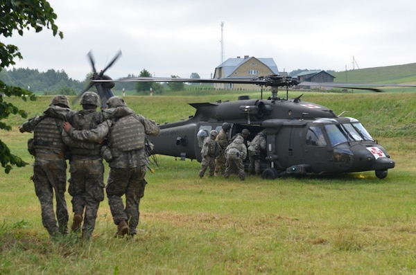 A combined forces squad featuring members of the Minnesota Army National Guard's 1st Armored Brigade Combat Team, 34th Infantry Division, British Royal Marines and Polish soldiers transport a simulated casualty to an HH-60M Black Hawk helicopter after a ground assault exercise transitioned into a medical evacuation exercise near Sventezeris, Lithuania, June 18, 2017. The training was part of Exercise Saber Strike 17, a U.S. Army Europe-led training exercise in the Baltic region. The exercise tests the capability of multiple nations to act against a threat.