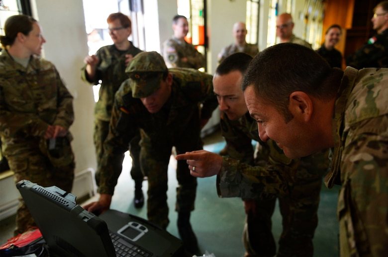 U.S. Air Force and German service members examine weather data on a computer at McCully Barracks, Germany, June 15, 2017. Ramstein's 7th Weather Squadron Airmen, along with allies from Germany, Poland, and Hungary, conducted Exercise Cadre Focus 17-1, where they aimed to enhance interoperability for joint missions. Cadre Focus is a biannual training program used by the 7th WS to certify its Airmen in common Soldier tasks to cooperate with the U.S. Army. (U.S. Air Force photo by Airman 1st Class Joshua Magbanua)