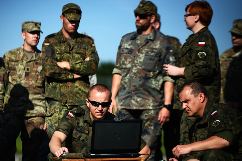 Polish Air Force Warrant Officer Marcin Galek, a weatherman, front left, operates a computer used for collecting weather data at McCully Barracks, Germany, June 15, 2017. Troops from Germany, Poland, and Hungary joined 7th Weather Squadron Airmen for Exercise Cadre Focus 17-1. This is the second year NATO allies participated in the exercise. (U.S. Air Force photo by Airman 1st Class Joshua Magbanua)