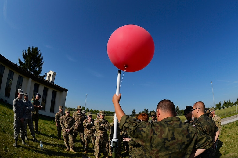 U.S. Airmen and NATO service members watch a weather balloon presentation conducted by Polish Air Force troops at McCully Barracks, Germany, June 15, 2017. Ramstein's7th Weather Squadron invited allies from Germany, Poland, and Hungary to participate in Exercise Cadre Focus 17-1. Participants exchanged information about how they conduct weather-related operations. (U.S. Air Force photo by Airman 1st Class Joshua Magbanua)