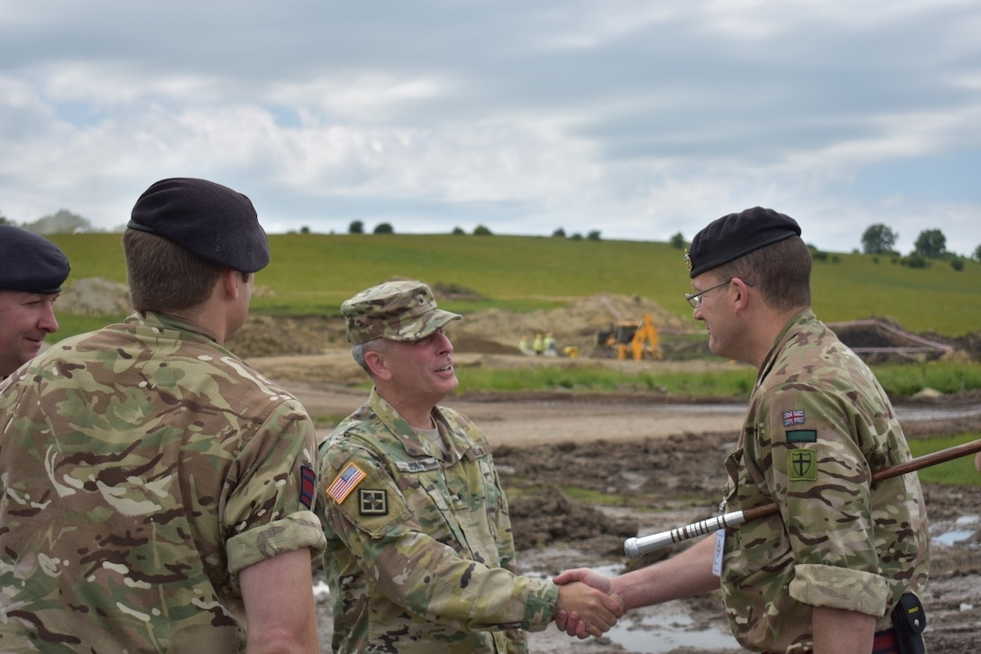 Company Sergeant Major John Ohara, U.K. Royal Monmouthshire Royal Engineers-Militia, welcomes Brig. Gen. Phillip S. Jolly to his worksite at the Joint National Training Center, Cincu, Romania. The Royal Engineers are in charge of building infrastructure for a sniper range as part of Operation Resolute Castle 2017.  Resolute Castle is an exercise strengthening the NATO alliance and enhancing its capacity for joint training and response to threats within the region.