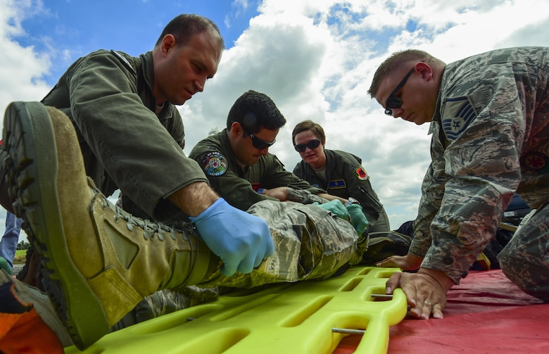 U.S. Air Force medical personnel from the 110th Bomb Squadron and the 37th Expeditionary Bomb Squadron, and firefighters, roll a volunteer onto a gurney during an exercise at Royal Air Force Fairford, U.K., June 13, 2017. Exercises involving multiple departments provide opportunities to increase interoperability and readiness. (U.S. Air Force photo by Airman 1st Class Randahl J. Jenson)