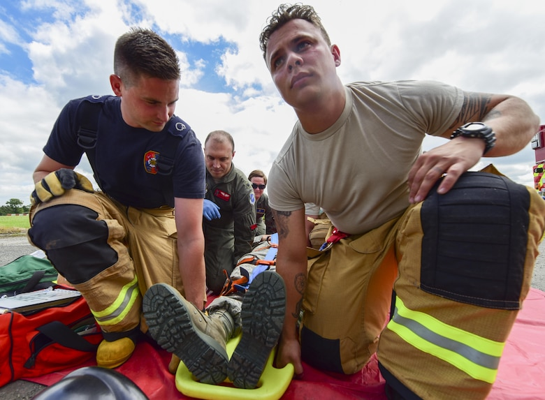 U.S. Air Force firefighters, as well as medical personnel and Royal Air Force Fairford Firefighters, work together to lift a gurney during a medical exercise at RAF Fairford, U.K., June 13, 2017. Exercises like this increase interoperability between the two departments and prepare them to work together during real-life scenarios. (U.S. Air Force photo by Airman 1st Class Randahl J. Jenson)