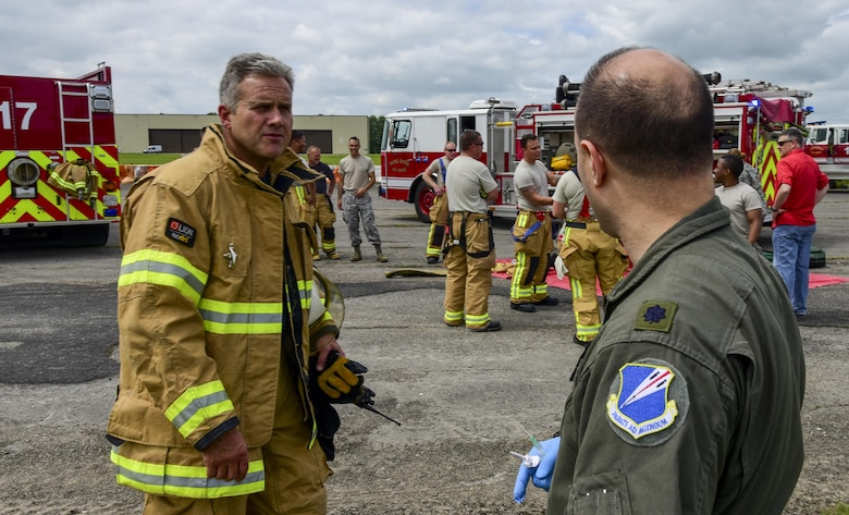 Trevor Daily, Royal Air Force assistant fire chief, debriefs with U.S. Air Force Lt. Col. Joseph Fugaro, 110th Bomb Squadron flight surgeon, after a medical exercise at RAF Fairford, U.K., June 13, 2017. Exercises like this increase interoperability between the two departments and prepare them to work together during real-life scenarios. (U.S. Air Force photo by Airman 1st Class Randahl J. Jenson)