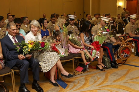 Flowers are presented to the family of Maj. David P. Tumanjan, out-going commanding officer of Recruiting Station Fort Lauderdale, and Maj. Marcus D. Gillett, the on-coming commanding officer of the recruiting station, during a change of command ceremony held at the Double Tree Hotel in Sunrise, Florida, June, 9, 2017. Tumanjan commanded the recruiting station for 36 months before relinquishing his command. (U.S. Marine Corps photo by Sgt. Andy J. Orozco)