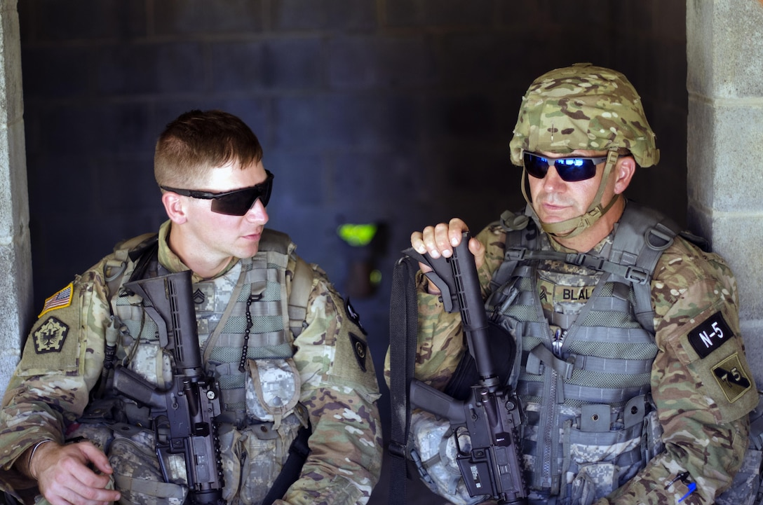 Sgt. Jonathan Anderson a Combat Engineer representing the 83rd U.S. Army Reserve Readiness Center, and Sgt. David Blalock a Cable Systems Installer-Maintainer representing the 75th Training Command, share a brief moment in the shade during Combat Skills Testing Lanes at the 2017 U.S. Army Reserve Best Warrior Competition at Fort Bragg, N.C. June 14. This year's Best Warrior Competition will determine the top noncommissioned officer and junior enlisted Soldier who will represent the U.S. Army Reserve in the Department of the Army Best Warrior Competition later this year at Fort A.P. Hill, Va. (U.S. Army Reserve photo by Sgt. William A. Parsons) (Released)