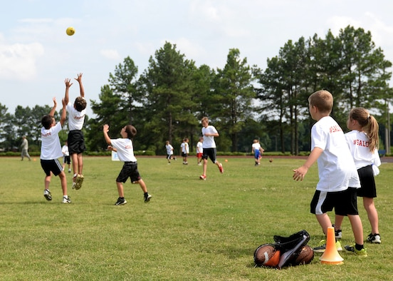 Children from the Proctor & Gamble Andre Roberts Football ProCamp play football June 16, 2017, at Little Rock Air Force Base, Arkansas. Andres Roberts, an Atlanta Falcons wide receiver and former military child, worked side by side with volunteers to help teach children different football skills. (U.S. Air Force photo by Airman 1st Class Codie Collins)