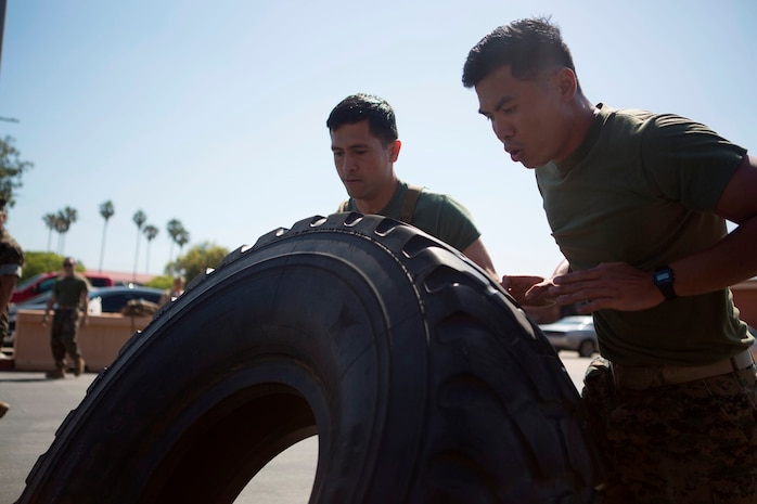 U.S. Navy Petty Officer Third  Class Julian Eledia, Hugo Reaendez, Corpsmen with 1st Medical Battalion, 1st Marine Logistics Group, participate in a tire flip contest during the North County Corpsman Cup on Camp Pendleton, Calif., June 16, 2017. The North County Corpsman Cup is designed to test the knowledge, physical readiness and teamwork of each participating sailor while promoting esprit de corps among the Hospital Corpsman community. (U.S. Marine Corps photo by Lance Cpl. Joseph Sorci)
