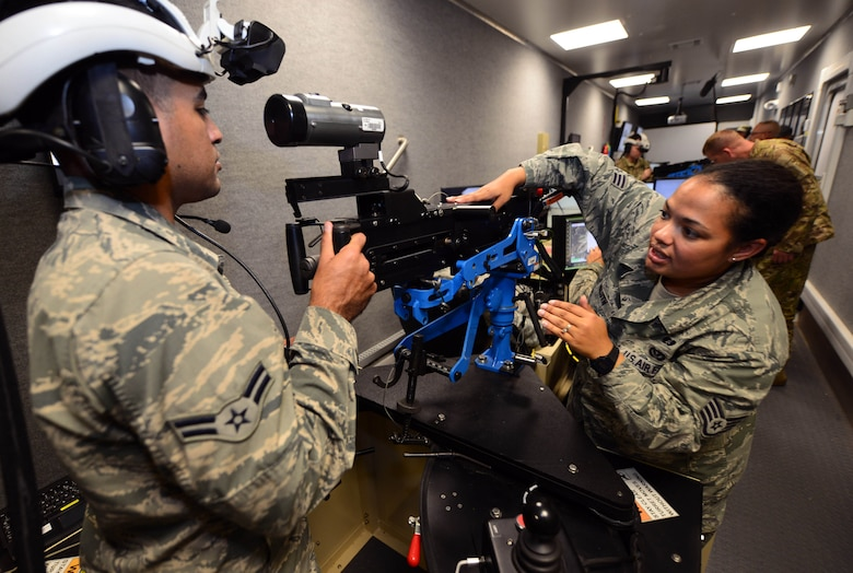 U.S. Air Force Staff Sgt. Jessica Gluth, an emergency management journeyman assigned to the 28th Civil Engineer Squadron, Ellsworth Air Force Base, S.D., explains the gunner position of a virtual convoy trainer to U.S. Air Force Airmen 1st Class Joshua Torres, a power production journeyman assigned to the 28th CES, at Camp Rapid, S.D., June 15, 2017. The virtual convoy trainer is housed inside a trailer and consists of four Humvee stations, each with a place for a driver and gunner. (U.S. Air Force photo by Airman 1st Class Donald C. Knechtel)