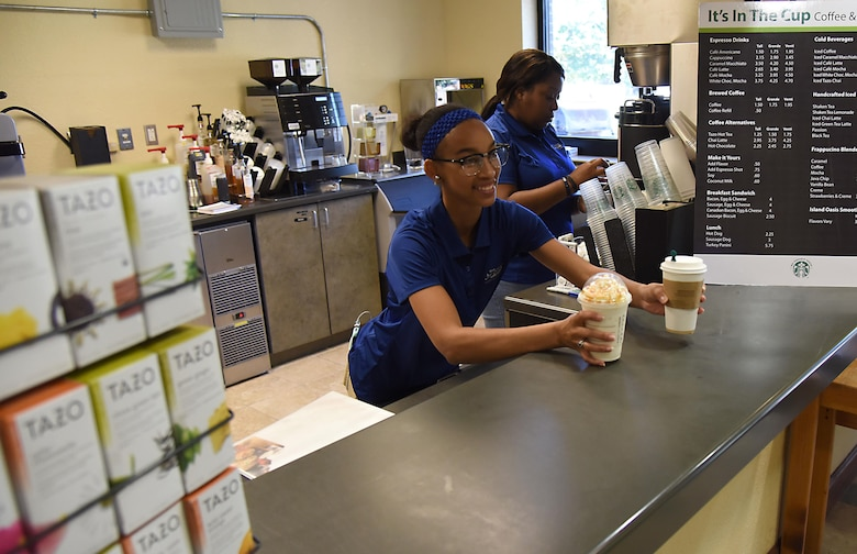"""Quiana James and Teaunda Rodgers, 81st Force Support Squadron sales clerks, serve and prepare orders at """"It Is In The Cup"""" in the Bay Breeze Event Center June 8, 2017, on Keesler Air Force Base, Miss. Keesler's new coffee & smoothie bar will have its grand opening on June 29 at the Bay Breeze Event Center. The facility proudly serves Starbucks coffee, Frappuccino's, iced beverages and espresso as well as Island Oasis smoothies in a variety of flavors. A full menu of items can be found at keesler81fss.us. (U.S. Air Force photo by Kemberly Groue)"""