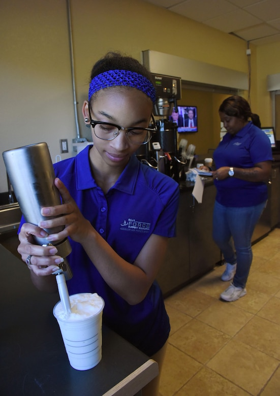 """Quiana James and Teaunda Rodgers, 81st Force Support Squadron sales clerks, prepares orders at """"It Is In The Cup"""" in the Bay Breeze Event Center June 8, 2017, on Keesler Air Force Base, Miss. Keesler's new coffee & smoothie bar will have its grand opening on June 29 at the Bay Breeze Event Center. The facility proudly serves Starbucks coffee, Frappuccino's, iced beverages and espresso as well as Island Oasis smoothies in a variety of flavors. A full menu of items can be found at keesler81fss.us. (U.S. Air Force photo by Kemberly Groue)"""