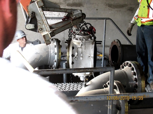Workers remove a 14-inch double-block and bleed valve as part of DLA's closure of Defense Fuel Support Point San Pedro.