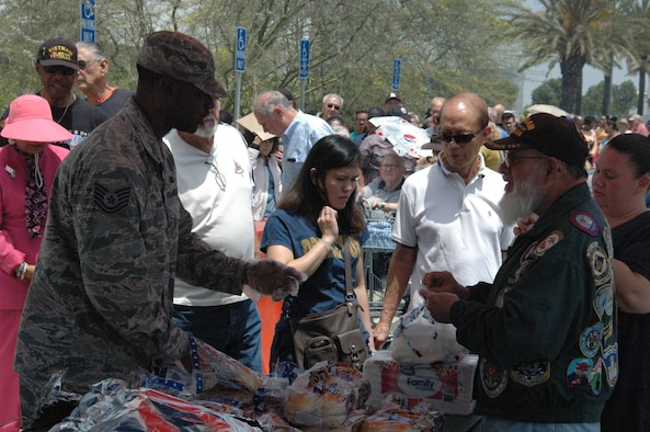 """Tech. Sgt. Gregory Reid from the 61st Communications Squadron and a volunteer with the """"Rising Six"""" service group at the Space and Missile Systems Center, prepares to serve the first of nearly 750 attendees during a """"Burger Burn"""" as part of the annual Armed Forces Retiree Appreciation Day, June 3, 2017, at Los Angeles Air Force Base in El Segundo, California. (U.S. Air Force photo/ James Spellman, Jr.)"""