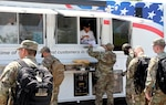 Soldiers from the Marne Reception Center put in their lunch orders at the Outpost food truck and wait to be served. The food truck is a convenient way for soldiers to get chow on the go.