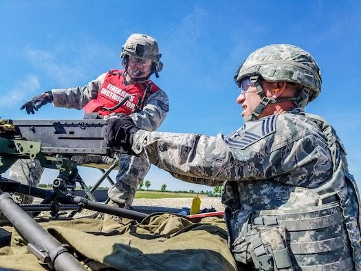 U.S. Staff Sgt. Troy Green (left), a combat arms instructor with the 139th Security Forces Squadron, Missouri Air National Guard, gives instruction to Chief Master Sgt. Mark Richie, while firing a M2 50-caliber machine gun, during a live-fire training exercise at Fort Riley, Kan., June 7, 2017. The live-fire machine gun training is an annual requirement for members of security forces and support personnel. (U.S. Air National Guard photo by Tech. Sgt. Christopher Black)