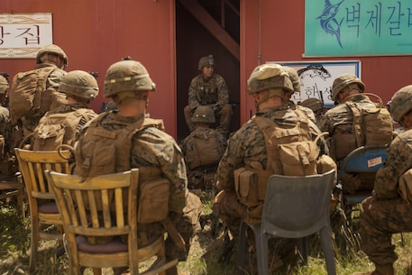 MARINE CORPS BASE HAWAII – Cpl. Aaron Yoshimura, a squad leader with Kilo Company, 3rd Battalion, 3rd Marine Regiment, briefs his squad on the 'Recon, Isolation, Secure a foothold and Seize the objective' process for his Marines during Exercise Bougainville 1-17.2 aboard Marine Corps Base Hawaii, June 17, 2017. The unit went over procedures and the basics of their roles as infantrymen for Exercise Bougainville, a two-week training exercise to enhance their lethality and effectiveness as a force in readiness. Kilo Co. conducted Military Operation in Urban Terrain training in which Marines practiced clearing buildings, wrapping tourniquets on simulated wounds, weapon drills and lessons on urban tactics. (U.S. Marine Corps photo by Cpl. Jesus Sepulveda Torres)
