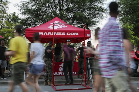 Riverbend Festival attendees observe the Marines booth in Chattanooga, Tennessee, June 10, 2017. Marines challenged Riverbend Festival attendees to do as many Marine Corps pull-ups as they could. (U.S. Marine Corps photo by Sgt. Mandaline Hatch)