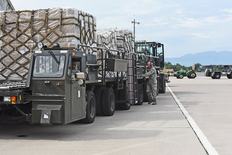 Technical Sgt. Jonathan Rasmussen, small air terminal section chief at Joint Task Force-Bravo, guides two of his teammates as they load cargo onto a truck at Soto Cano Air Base, June 13, 2017. The supplies the small air terminal handles vary from medication, food and supplies to meet service members' needs on base, to humanitarian assistance supplies received through the U.S. Agency for International Development's Denton Program.