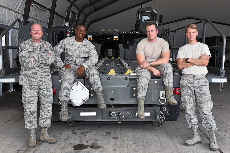 Technical Sgt. Jonathan Rasmussen (far left), small air terminal section chief at Joint Task Force-Bravo, poses for a photograph with his teammates at Soto Cano Air Base, June 13, 2017. Their call to duty includes supporting the Denton Cargo mission, in which humanitarian supplies are sent to countries in need through the U.S. Agency for International Development, support to service member rotations as by receiving cargo and new personnel upon arrival to Soto Cano Air Base, as well as supporting a weekly rotating mission in which a C130 aircraft brings in supplies such as food and medication from Charleston Air Force Base. These supplies go to the dining facility and other entities at JTF-Bravo to ensure that all service members' needs are covered.