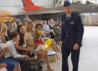 Carla Abba glances down at the bouquet of flowers from her husband, Col. David Abba, the new 53rd Wing commander, during his change of command June 20 at EglinAir Force Base, Fla. The wing also welcomed their children. Nyah, Jack, Serena, Lauren and Lani Abba. (U.S. Air Force photo/Ilka Cole)