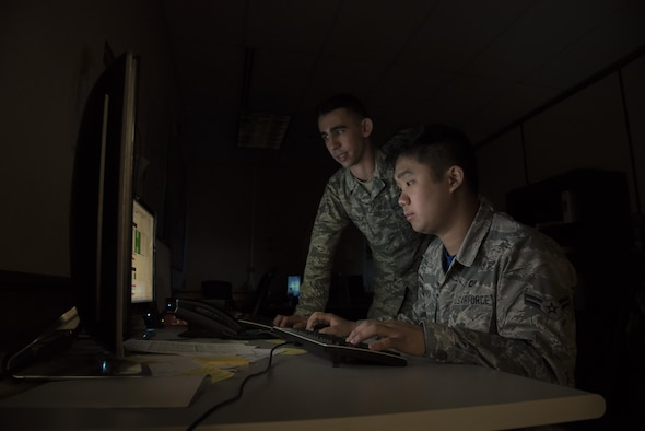 U.S. Air Force Senior Airman Joseph Goebel, left, and Airman 1st Class Anthony Ohara, right, both 35th Operations Support Squadron weather forecasters, analyze climate patterns during RED FLAG-Alaska 17-2 at Eielson Air Force Base, Alaska, June 16, 2017. Goebel and Ohara were in charge of running the weather flight for RF-A, which consisted of seven other Air National Guardsman from Joint Base Lewis-McChord, Washington. (U.S. Air Force photo by Airman 1st Class Sadie Colbert)