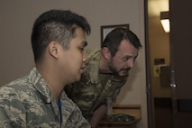 U.S. Air Force Airman 1st Class Anthony Ohara, a 35th Operations Support Squadron weather forecaster, briefs Royal Danish Army Capt. Andreas Otterstoem, a 116th Air Support Operations Squadron joint terminal attack controller, on the weather forecast for the day during RED FLAG-Alaska 17-2, at Eielson Air Force Base, Alaska, June 16, 2017. Misawa's weather Airmen briefed other nations including the Royal Thai Air Force, Republic of Korea and the Japan Air Self-Defense Force. (U.S. Air Force photo by Airman 1st Class Sadie Colbert)