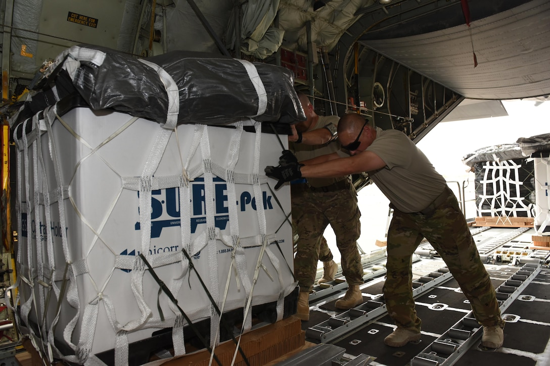 Senior Airman John Cox, an air transportation specialist with the 386th Expeditionary Logistics Readiness Squadron, and Chief Master Sgt. James Traficante, a loadmaster with the 737th Expeditionary Airlift Squadron, work together to push a container delivery system into the cargo bay of a C-130 Hercules in preparation for an air drop at an undisclosed location in Southwest Asia, over the weekend. Providing the fuel that keeps the fight going, the 386th Air Expeditionary Wing has delivered more than 80 tons of food, water and other supplies to various supported forces throughout the U.S. Air Forces Central Command area of responsibility in support of Combined Joint Task Force - Operation Inherent Resolve ground troops. (U.S. Air Force photo/Tech. Sgt. Jonathan Hehnly)