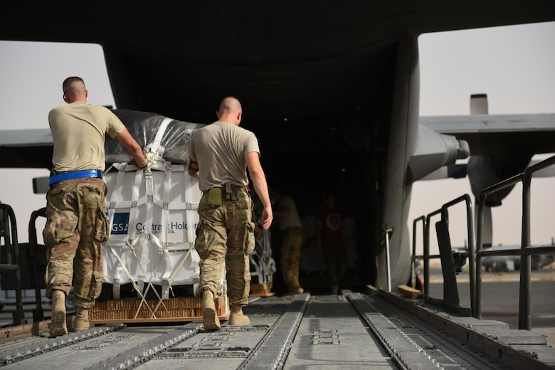 Air transportation specialists with the 386th Expeditionary Logistics Readiness Squadron push a container delivery system off a 60k Tunner loader and into the cargo bay of a C-130 Hercules in preparation for an air drop at an undisclosed location in Southwest Asia, over the weekend. Providing the fuel that keeps the fight going, the 386th Air Expeditionary Wing has delivered more than 80 tons of food, water and other supplies to various supported forces throughout the U.S. Air Forces Central Command area of responsibility in support of Combined Joint Task Force - Operation Inherent Resolve ground troops. (U.S. Air Force photo/Tech. Sgt. Jonathan Hehnly)
