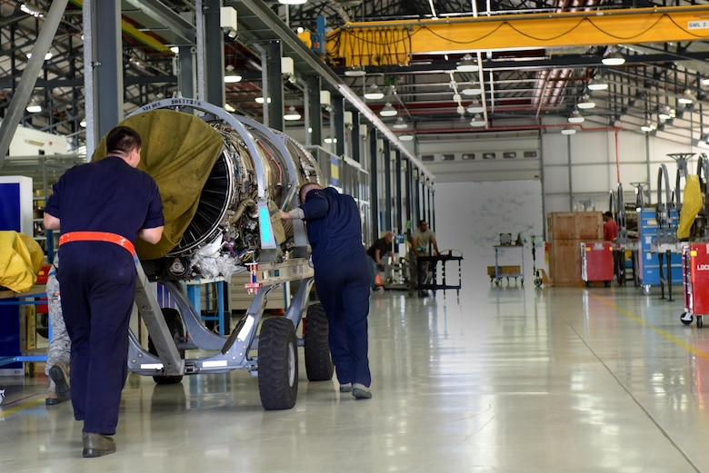 Airmen assigned to the 48th Component Maintenance Squadron push an F-15 engine in to the propulsions shop at Royal Air Force Lakenheath, England, June 13. Part of the 48th CMS's responsibilities include the routine maintenance of F-15 engines. (U.S. Air Force photo/Airman 1st Class Eli Chevalier)