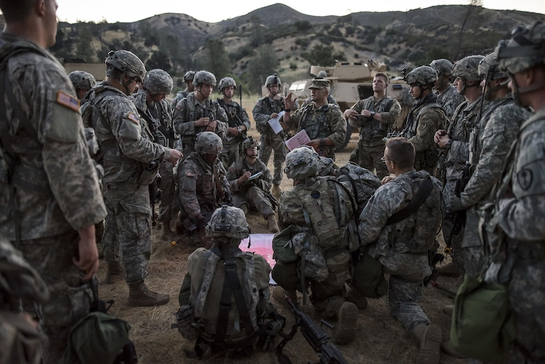 A platoon of U.S. Army Reserve Soldiers from the 339th Military Police Company (Combat Support), headquartered in Davenport, Iowa, conducts a convoy brief prior to a route reconnaissance mission at a Warrior Exercise (WAREX) held at Fort Hunter Liggett, California, June 20. The MP company's Soldiers had to relocate their tactical assembly areas in the field multiple times as they reconnoitered different areas of their operational environment, while fighting against temperatures reaching 100-plus degrees daily. (U.S. Army Reserve photo by Master Sgt. Michel Sauret)