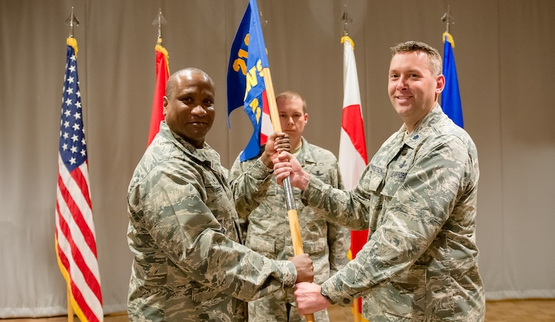 Col. Devin Pepper, 21st Operations Group commander, hands the 12th Space Warning Squadron guidon Lt. Col. Carl Bottolfson at a change of command ceremony, June 8, 2017, at Thule Air Base, Greenland. The 12th SWS provides critical, real-time warning of ballistic missile attacks against North America and detects, tracks and identifies earth-orbiting objects in support of U.S. Strategic Command's space control mission. (Courtesy Photo)