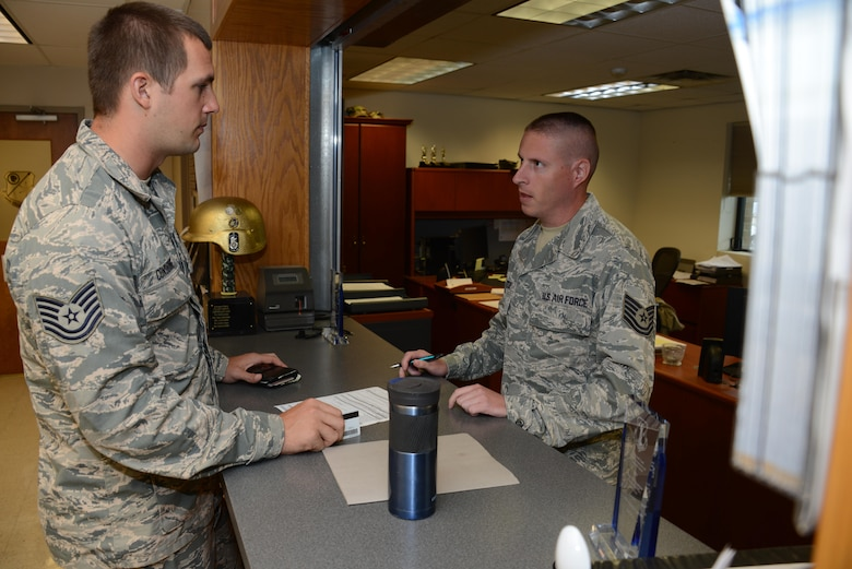 Tech. Sgt. Mike Considine talks with Tech. Sgt. Mike Winter who is a Travel Pay Technician with the Iowa Air National Guard's 185th Air Refueling Wing at the Wing's Financial Management Office in Sioux City, Iowa on June 21, 2017. 