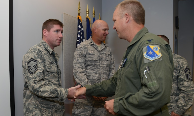 185th Air Refueling Wing Commander Col. Larry Christensen presents Senior Master Sgt. Joe Donovan of the 185th Financial Management office with Commanders coin at the Sioux City, Iowa Air National Guard base on June 21, 2017. Donovan and the rest of the Financial Management office were given coins in recognition of their receiving two top financial management awards for achievement and mission impact. 