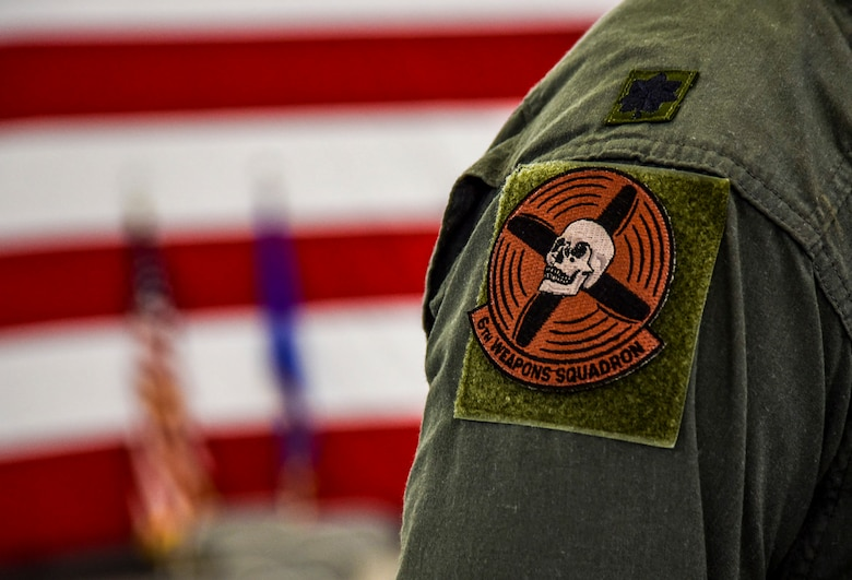 Lt. Col. Michael Blauser, 6th Weapons Squadron commander, displays the 6th WPS patch. The patch has represented the squadron since 1917 and features a skull at the center of spinning propellers. (U.S. Air Force photo by Airman 1st Class Andrew D. Sarver/Released)