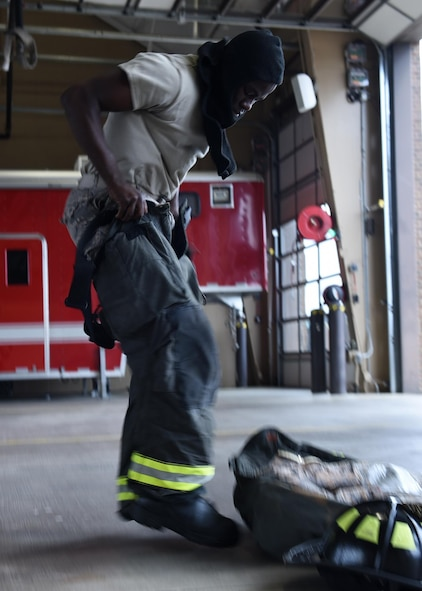 Airman 1st Class Tevado Beckford, 19th Civil Engineer Squadron Fire Protection apprentice, dons his fire gear in 39 seconds June 13, 2017, at Little Rock Air Force Base, Ark. The 19th CES Fire Department firefighters respond to fires or emergency situations on base at a moment's notice. (U.S. Air Force photo by Airman 1st Class Kevin Sommer Giron)