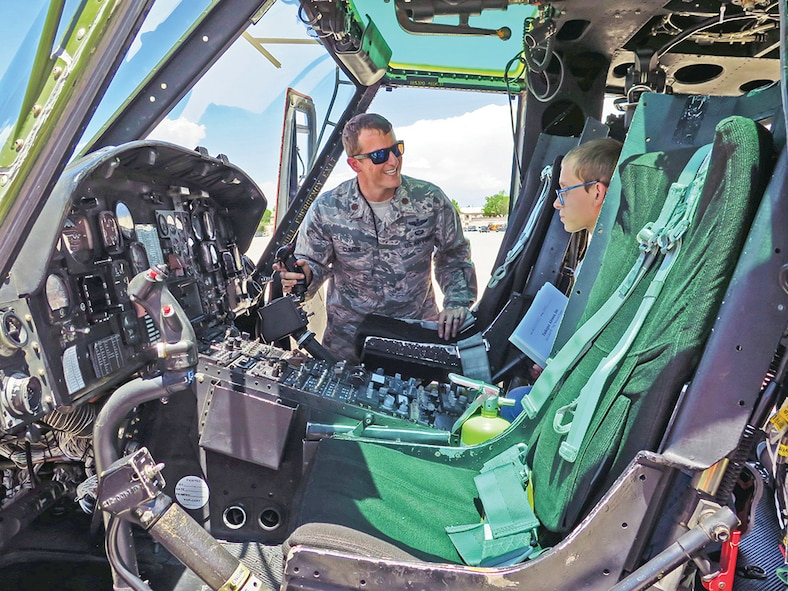 Maj. Frank Cumble, 58th Special Operations Wing, shows Seth Knudsen around the cockpit of a Huey helicopter on Kirtland's flightline.
