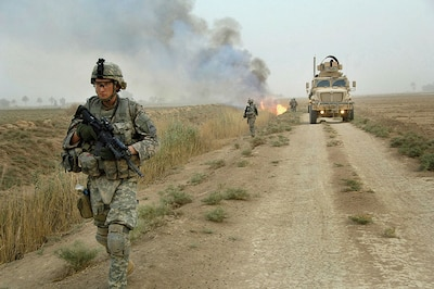 Soldiers assigned to Task Force 1-35 Armor, 2nd Brigade Combat Team, 1st Armored Division, make their way down road as canal burns in Tahwilla, Iraq, July 30, 2008 (U.S. Army/David J. Marshall)