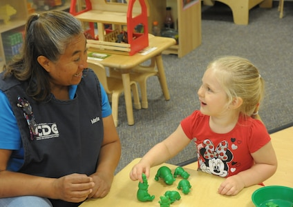 Maria Lopez, Child Development Center, child and youth program assistant, teaches Naomi Burton about colors and numbers, June 19, at Joint Base San Antonio-Randolph.  The CDP welcomes children between the ages of 6 weeks and 5 years. The CDP provides activities and programs which support children's social, emotional, physical and intellectual development. The program is accredited by National Association for the Education of Young Children (NAEYC). The CDP is a USDA certified center, providing breakfast, lunch and two snacks each day.