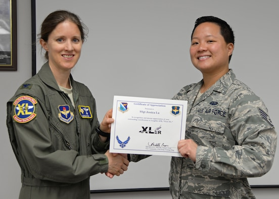 "Staff Sgt. Jessica Lu, 47th Communications Squadron client systems technician (right), accepts the ""XLer of the week"" award from Col. Michelle Pryor, 47th Flying Training Wing vice commander (left), at Laughlin Air Force Base, June 14, 2017. The ""XLer"" is given to those who consistently make outstanding contributions to their unit, Laughlin and the mission."