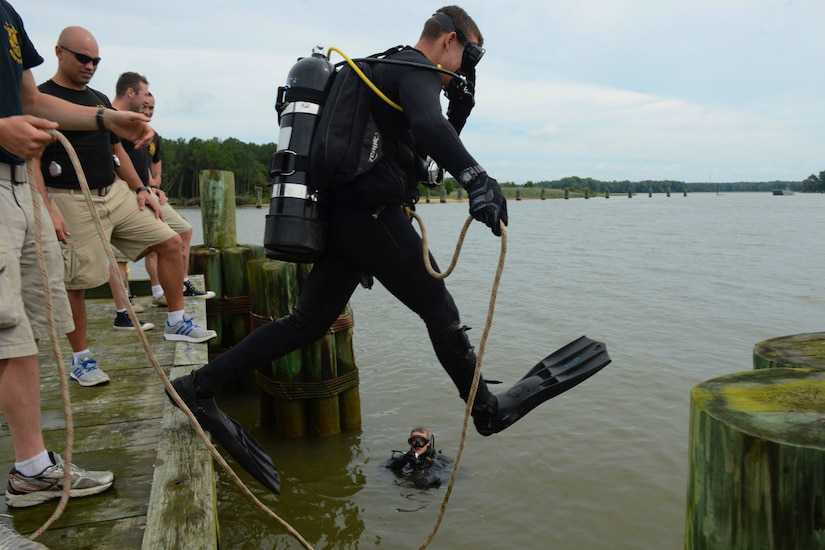 U.S. Army Pfc. Kyle Grimes, 74th Engineer Dive Detachment, 92nd Engineer Battalion second class diver, jumps into the James River to inspect Third Port's piers during a diving mission at Joint Base Langley-Eustis, Va., June 20, 2017. To prevent massive reconstruction projects to occur in the future, the divers look closely for any damage or irregularities they can easily fix while inspecting the piers. (U.S. Air Force photo/Airman 1st Class Kaylee Dubois)