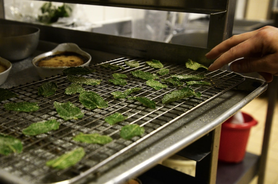 An Airman checks on candied mint leaves made during culinary training at the Gateway Dining Facility on RAF Mildenhall, England, June 8, 2017. Part of the weeklong training focused on encouraging creativity within the 100th Force Support Squadron members. Though cooks are required to follow a set menu, but they can add finesse and technique to food preparation. (U.S. Air Force photo by Senior Airman Justine Rho)