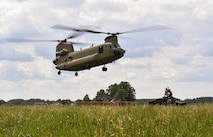 A U.S. Army CH-47 Chinook helicopter flies towards Airmen assigned to the 435th Contingency Response Group, Ramstein Air Base, Germany, during exercise Saber Strike 17 at Lielvarde Air Base, Latvia, June 10, 2017. The 435th CRG Airmen worked alongside U.S. Army and NATO military members throughout the exercise. Saber Strike 17 continues to increase participating nations' capacities to conduct a full spectrum of military operations. (U.S Air Force photo by Senior Airman Tryphena Mayhugh)
