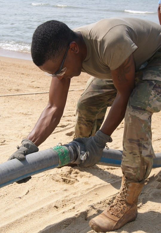 Spc. Donovan Stutts, member of the 40th Composite Supply Company water purification team, secures pipes together to pump salt water during the Reverse Osmosis Water Purification Unit Rodeo at Fort Story, Virginia, June 12, 2017.
