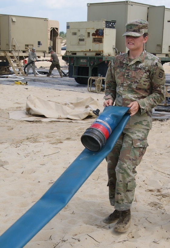 Private 1st Class Kayla Jacobs, member of the 249th Composite Supply Company water purification team, straightens a water hose during the Reverse Osmosis Water Purification Unit Rodeo at Fort Story, Virginia, June 13, 2017.