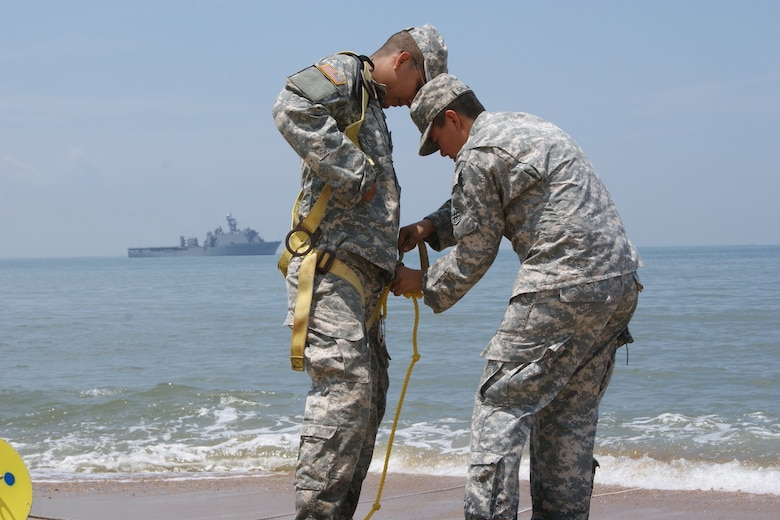 (Right) Sgt. Miriam Gallardo helps Spc. Javier Ramirez, both on the 961st Quartermaster Company water purification team, to prepare for entering the Atlantic Ocean as part of the Reverse Osmosis Water Purification Unit Rodeo at Fort Story, Virginia, June 13, 2017.