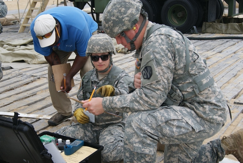 (Kneeling left to right) Spc. Brandi Madden and Spc. Scott Morin, members of the 125th Quartermaster Company water purification team, test salt water as a Forces Command Logistics Training Cluster evaluator assesses them at the Reverse Osmosis Water Purification Unit Rodeo at Fort Story, Virginia, June 15, 2017.