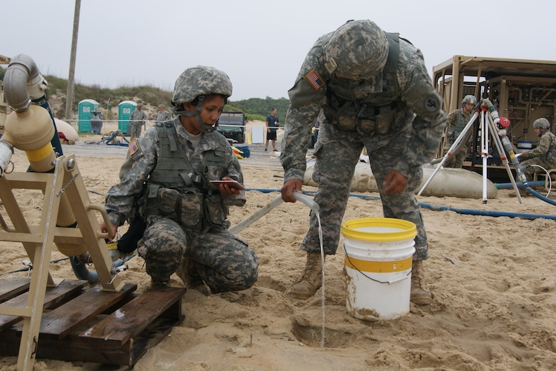 (Left to right) Sgt. Monika MacDonald and Private 1st Class Miguel Arroyo, members of the 753rd Quartermaster Company water purification team, drain the cyclone separator as they shut down operations at the Reverse Osmosis Water Purification Unit Rodeo at Fort Story, Virginia, June 15, 2017.