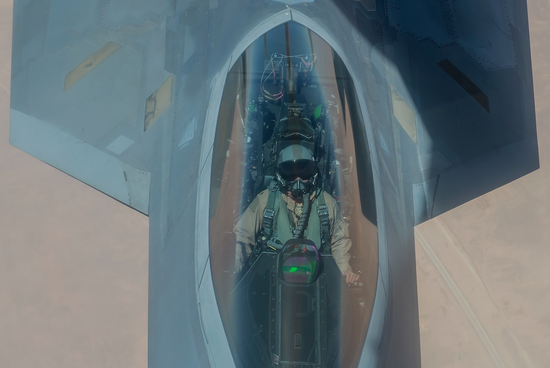 A U.S. Air Force F-22 Raptor pilot flies while his aircraft is refueled by a KC-135 Stratotanker above Southwest Asia June 21, 2017. The F-22, a component of the Global Strike Task Force, supports U.S. and coalition forces working to liberate territory and people under the control of ISIS. (U.S. Air Force photo by Staff Sgt. Trevor T. McBride)