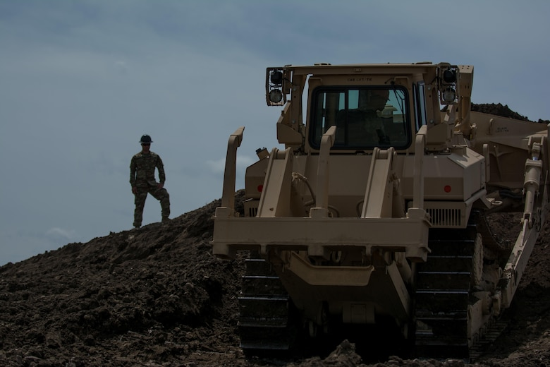 "Staff Sgt. Jonathan Kline, a horizontal construction supervisor with the 317th Engineer Company and project noncommissioned officer in charge, watches Pfc. Daniel Valdavenos operate a T-9/D7R medium dozer. Valdavenos is receiving ""stick time"" in order to re-familiarize himself with the equipment as the 317th prepares to take part in Innovative Readiness Training (IRT). The IRT project produces military readiness while simultaneously providing quality services to communities throughout the U.S. This particular project takes place on the Blackfeet Reservation in Browning, Montana during the months of June thru August (U.S. Army photo by Staff Sgt. Jason Proseus/released)."